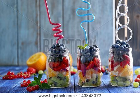 Glass jars with fruits and berries on wooden table