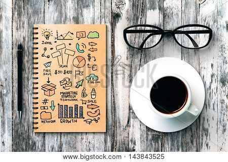 Top view of textured wooden desktop with business sketch in spiral notepad coffee cup glasses pen and paper clips