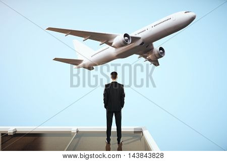 Traveling concept with businessman on roof looking at flying by airplane on sky background