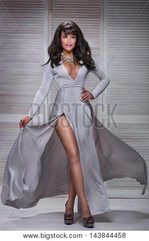 Elegant beautiful brunette lady posing in maxi dress. Indoor shot. Evening dress.