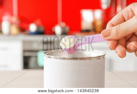 Woman hand is preparing baby formula in kitchen