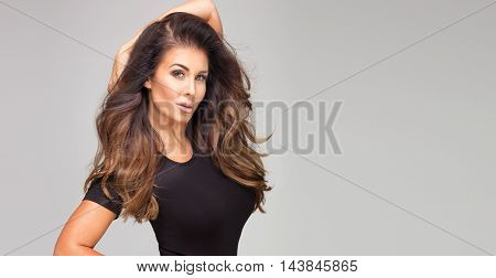 Attractive brunette woman with long hair posing in studio looking at camera.