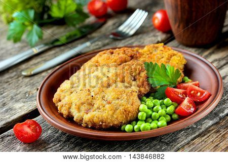 Delicious and hearty meal - fried steak in bread crumbs with tomatoes and green peas on a wooden table selective focus