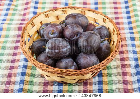 Wicker Basket With Ripe Plums On Tablecloth