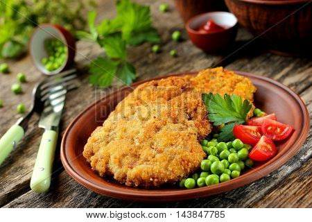 Pork cutlet in bread crumbs with tomatoes and green peas on a wooden table