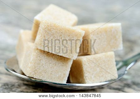 Beige sugar cubes in a silver spoon on wooden background