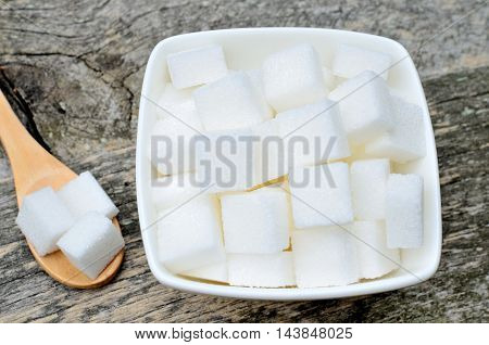 Sugar cubes in a ceramic bowl on wooden background