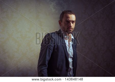 Young handsome and elegant man posing isolated over vintage background
