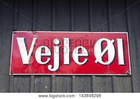 VEJLE DENMARK - AUGUST 22 2016: Danish vintage metal Vejle Beer signboard at a wall with old bricks on August 22 2016