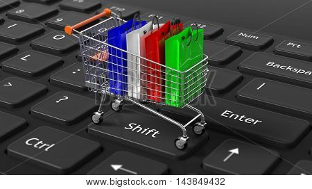 Silver shopping trolley with colorful bags on black computer keyboard