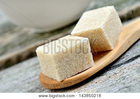 Beige sugar cubes in a wooden spoon on table