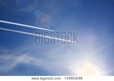 Two planes flying in parallel leaving behind a white trail blue sky clouds and a bright Sunny day