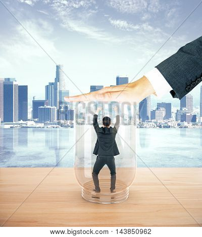 Stressed businessman miniature trapped inside transparent glass jar by employer. City background