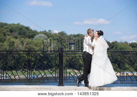 Wedding Couple Cuddling On The Bridge