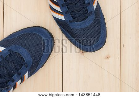 Sport shoes on a wooden floor background.