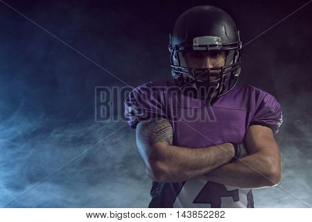 American football player on smoky background.