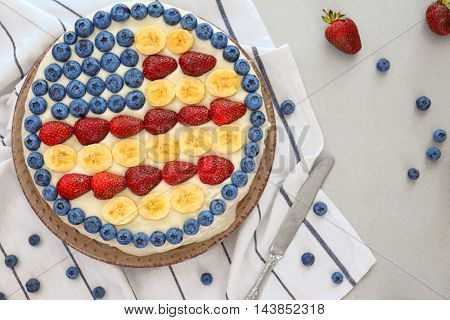 Patriotic American flag cake with berries and bananas on table