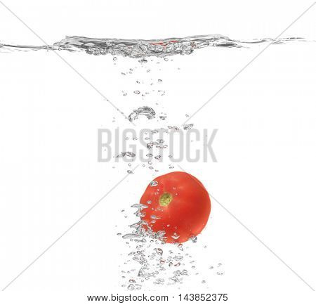 Fresh red tomato falling in water on white background