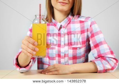 Young woman with glass of fresh juice sitting at the table