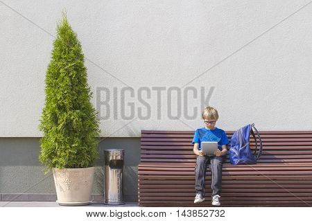 Schoolboy with tablet PC sitting on the bench near school. Outdoor. Education, technology people concept