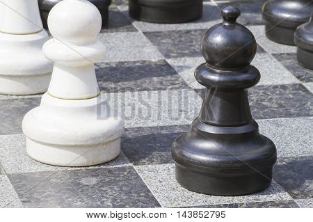 Close up of life sized chess pieces on chess board