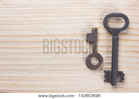 Real estate concept. Silver key with copy space for ad text and blank business note pad on wooden background. Top view