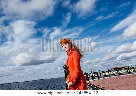 Fashionable woman in winter coat looking afar at autumn park.