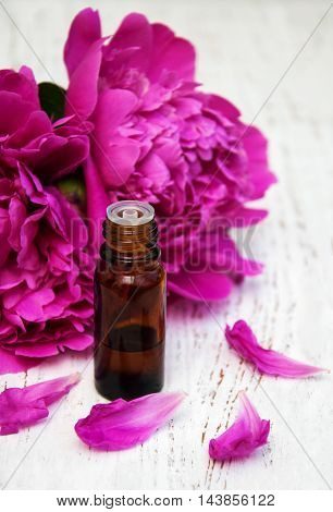 Peony flowers massage oils on a wooden background