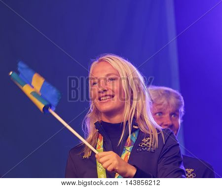 STOCKHOLM SWEDEN - AUG 21 2016: Happy swedish female wrestler Sofia Mattson waiving a flag when swedish olympic athletes are celebrated in Kungstradgarden Stockholm Sweden August 21 2016