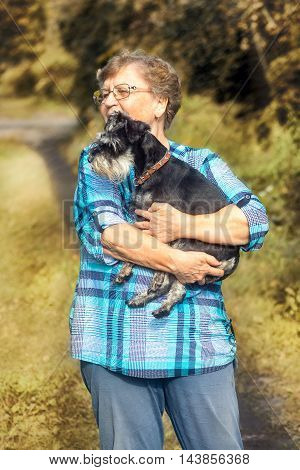 elderly woman standing on the background of autumn nature with a dog miniature schnauzer on hands