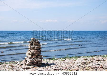 Stone sculpture by the beach with waves and blue water