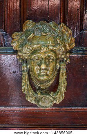 Door knocker in a shape of a human head on a wooden door