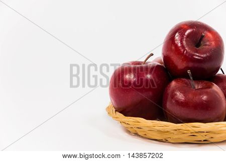 Close Up Of Ripe Red Apples In Wicker Basket Isolated On White Background