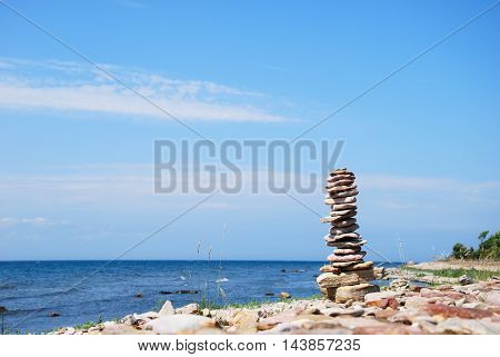 Balanced stone sculpture by the coast eith horizon and blue water