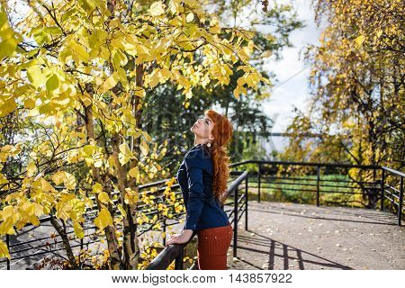 Young woman in autumnal park. Fashion nature beauty concept.