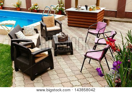 Backyard with pool and patio. Table and chairs, summer day.