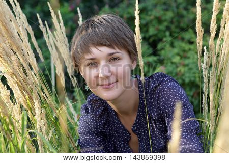 Portrait of a smiling woman in summer park