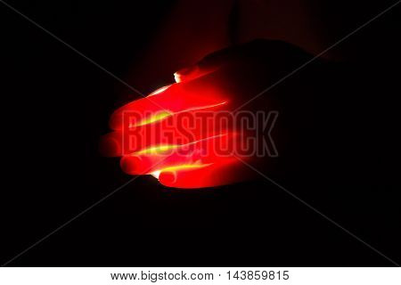 The red fiery flame in graceful female hands a plasma sphere in full darkness fingers is visible through