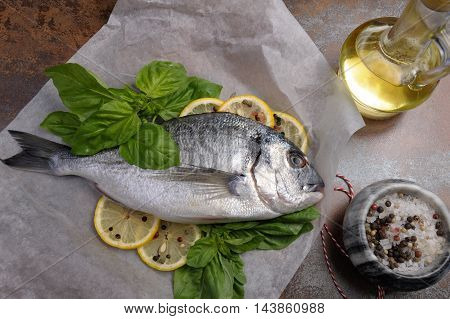 Raw fish Dorado with basil lemon slices on a piece of paper