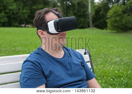 Man using virtual reality glasses in a park