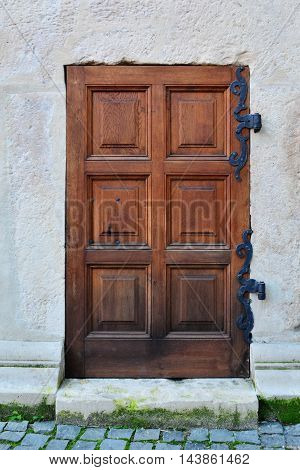 Old wooden door with decorative metal hinge