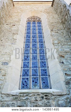 Stained glass window on old church wall exterior stone masonry.