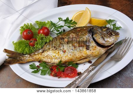 roasted fish Dorado with vegetables garnish and lemon slices on a plate
