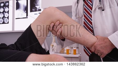 Senior caucasian doctor examining knee injury in his office