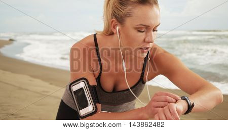 Woman runner checking fitness watch at the beach
