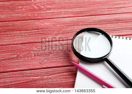 Magnifying Glass On A Red Wooden Table