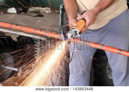 An unidentifiable man uses a grinding wheel to cut metal causing sparks