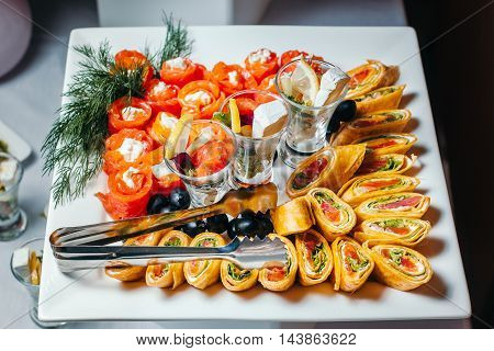 Salmon rolls stuffed with cheese sprinkled sesame seeds, laid on a white glass plate