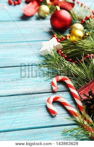Christmax Tree Branch With Baubles, Candies On Blue Wooden Table