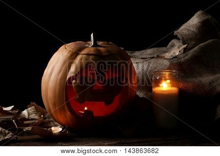 Halloween pumpkin with candle on brown wooden table